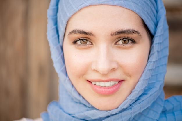 Gezicht van jonge lachende arabische vrouw in blauwe hijab op zoek naar jou