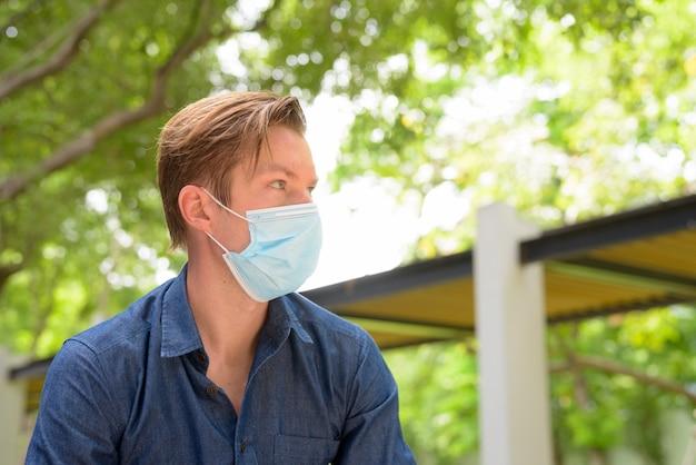 Gezicht van jonge man denken met masker voor bescherming tegen uitbraak van coronavirus in het park