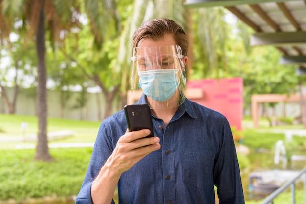 Gezicht van jonge man met behulp van telefoon met masker en gelaatsscherm voor bescherming tegen uitbraak van coronavirus in het park
