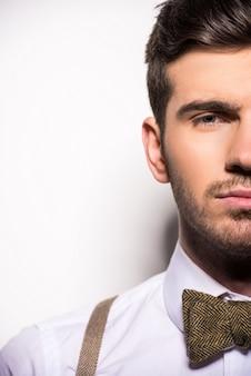 Gezicht van jonge man met bretels en strikje.
