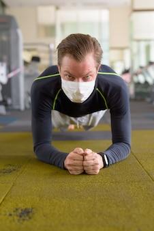 Gezicht van jonge man met masker doet plankpositie op de vloer bij sportschool tijdens coronavirus covid-19