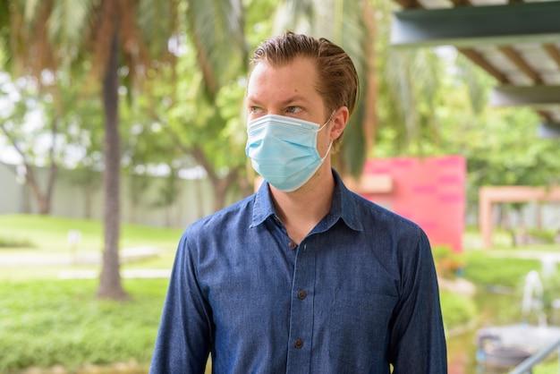 Gezicht van jonge man met masker voor bescherming tegen uitbraak van coronavirus denken in het park