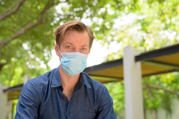 Gezicht van jonge man met masker voor bescherming tegen uitbraak van coronavirus in het park