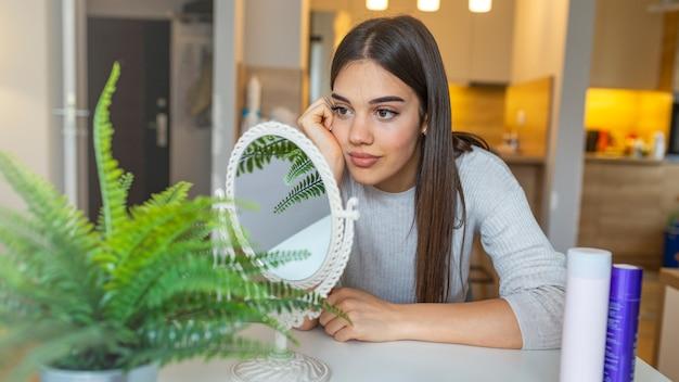 Gezicht van jonge mooie gezonde vrouw die in de spiegel kijkt.