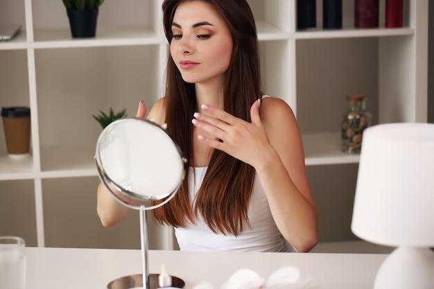 Gezicht van jonge mooie gezonde vrouw die in de spiegel kijkt