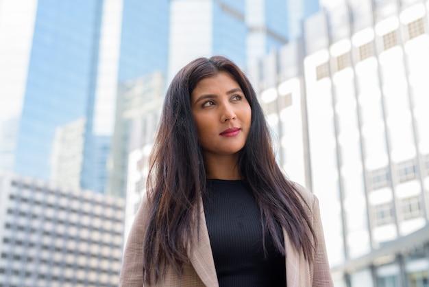 Gezicht van jonge mooie indiase onderneemster die op mening van de stad denkt