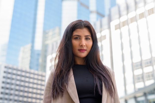 Gezicht van jonge mooie indiase zakenvrouw met uitzicht op de stad