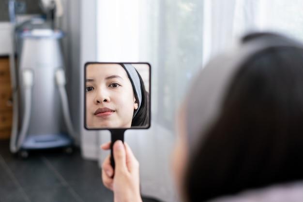 Gezicht van jonge vrouw en reflectie in de spiegel. na of voor plastische esthetische gezichtschirurgie in schoonheidskliniek.