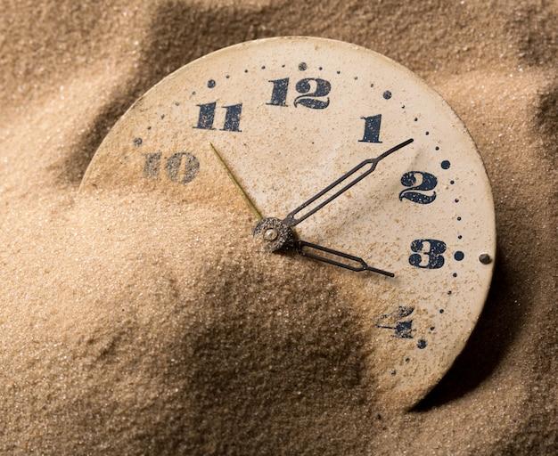 Gezicht van klok in zand