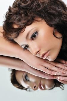 Gezicht van mooie gezonde vrouw en haar gedachtengang in de spiegel