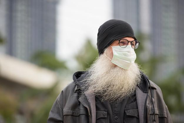 Gezicht van volwassen bebaarde hipster man met masker denken buitenshuis