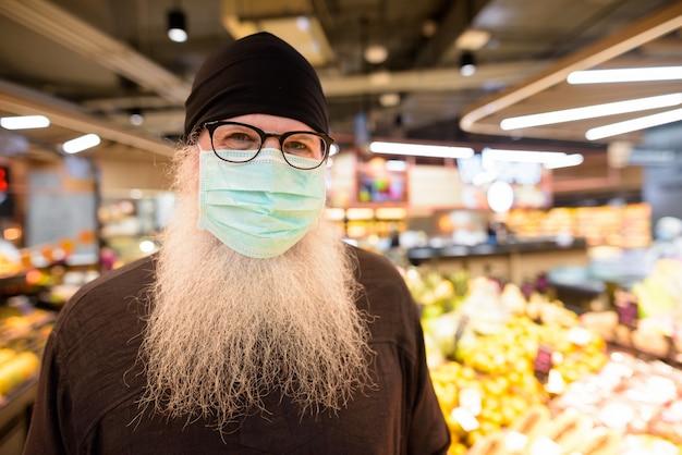 Gezicht van volwassen bebaarde hipster man met masker sociale afstand in de sectie fruit in de supermarkt