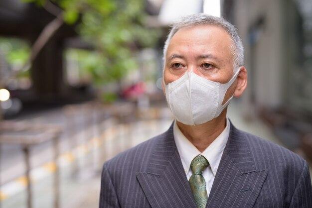 Gezicht van volwassen japanse zakenman met masker denken in de stad