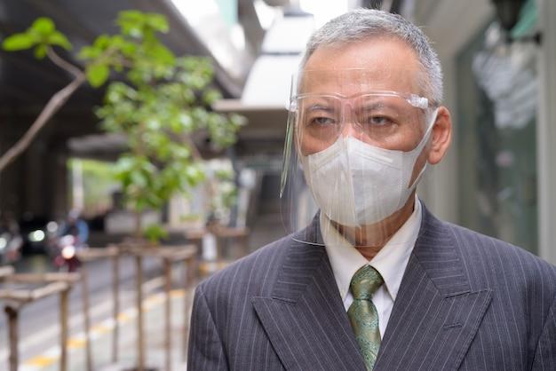 Gezicht van volwassen japanse zakenman met masker en gezicht schild denken in de stad