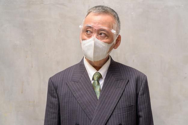 Gezicht van volwassen japanse zakenman met masker en gezicht schild denken