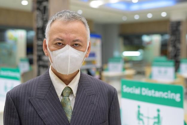 Gezicht van volwassen japanse zakenman met masker sociale afstand op de food court