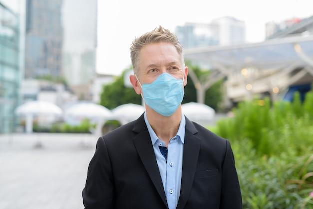 Gezicht van volwassen zakenman denken met masker voor bescherming tegen uitbraak van coronavirus in de stad buitenshuis
