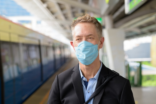 Gezicht van volwassen zakenman met masker denken en wachten op het luchttreinstation