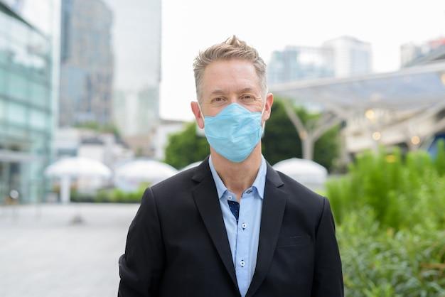 Gezicht van volwassen zakenman met masker voor bescherming tegen uitbraak van coronavirus in de stad buitenshuis