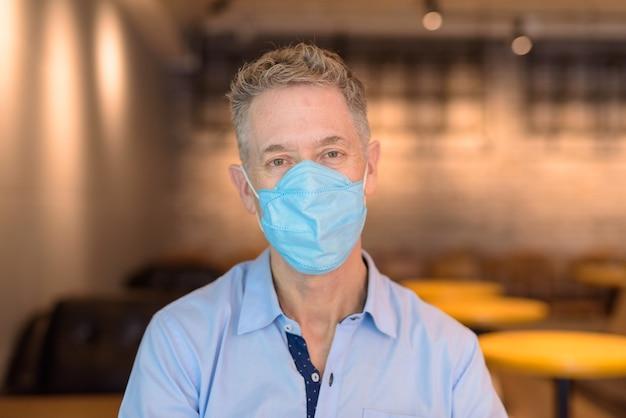Gezicht van volwassen zakenman met maskerzitting met afstand binnen de coffeeshop