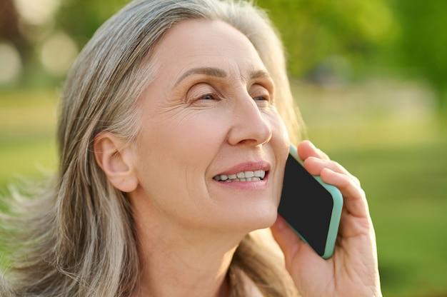 Gezicht van vrouw van pensioengerechtigde leeftijd praten op smartphone
