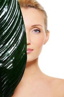 Gezicht van vrouw verstopt achter het grote groene blad