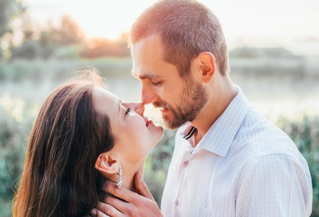 Gezichten van een jong meisje en een jongen in een kus en omhelzing