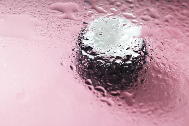 Gezichts- en handcrème onder een glazen oppervlak met water op een roze achtergrond