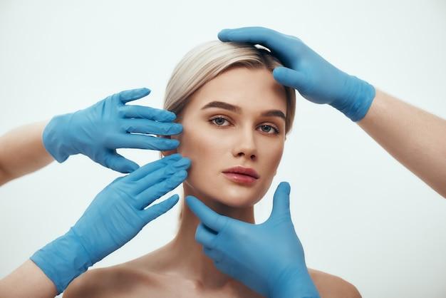Gezichtschirurgie mooie blonde vrouw die wacht op gezichtschirurgie terwijl chirurgen in blauwe medische