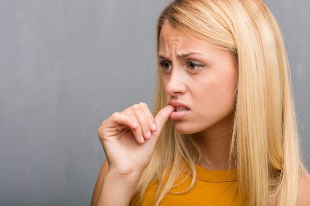 Gezichtsclose-up, portret van een natuurlijke jonge blonde vrouw het bijten spijkers