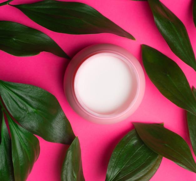 Gezichtscrème en groene bladeren