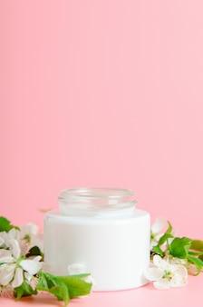 Gezichtscrème in witte pot op een roze achtergrond met witte bloemen. concept natuurlijke cosmetica, biologische schoonheid. kopieer ruimte.