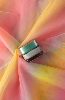 Gezichtsgroene kleimaskerpot voor schoonheidsproductmodel op kleurrijke regenboogorganzastof. gezondheidszorg huidverzorging hygiëne concept