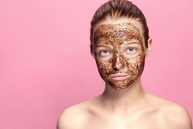 Gezichtshuid scrub. portret van sexy glimlachende vrouwelijke model toepassing van natuurlijke koffie masker, gezicht schrobben op gezichtshuid. close-up van mooie gelukkige vrouw met gezicht bedekt met schoonheidsproduct.
