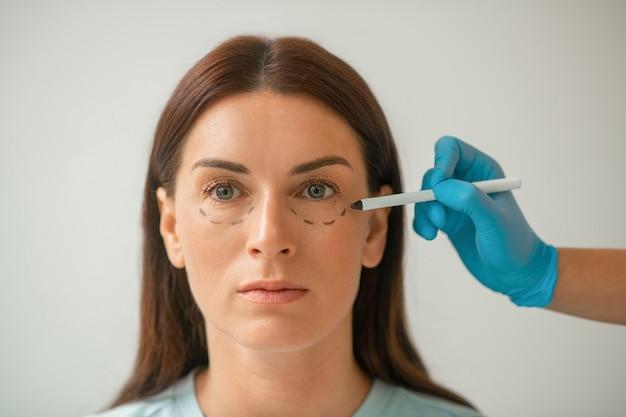 Gezichtslift. schoonheidsspecialist die lijnen trekt op het gezicht van de vrouw voor tilprocedures