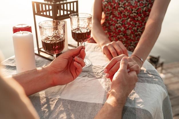 Gezichtsloos portret van een paar dat samen tijd doorbrengt met het drinken van wijn buiten: man die de hand van zijn vriendin vasthoudt en een verlovingsring doet die een huwelijksaanzoek doet. mooie huwelijksaanzoek ceremonie, er hangt liefde in de lucht