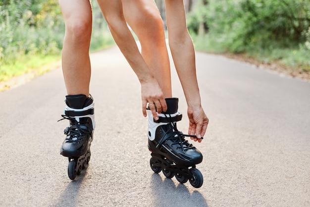 Gezichtsloos portret van een vrouw die rolschaatsen vastbindt terwijl ze buiten in het zomerpark op de asfaltweg aan het skaten is, onbekende vrouwelijke persoon die alleen rolschaatst.