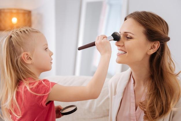 Gezichtsmake-up. vrolijk aangenaam blond meisje houdt een penseel vast en brengt poeder aan tijdens het doen van make-up voor haar moeder