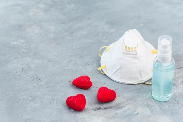 Gezichtsmasker en handgel op concrete achtergrond