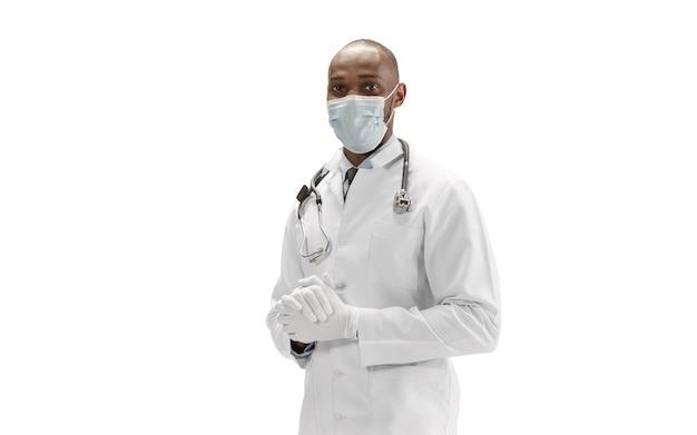 Gezichtsmasker en handschoenen. afro-amerikaanse arts op witte achtergrond, professioneel beroep. dagelijks hard werken voor de gezondheid en het redden van levens. portret op halve lengte. geneeskunde, gezondheidszorg, beroep concept.