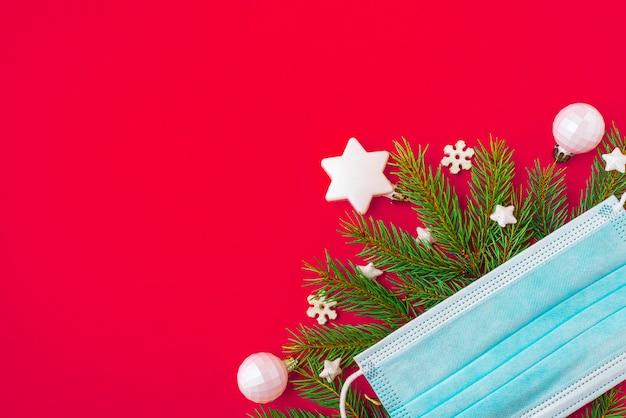 Gezichtsmasker fir tree en decoraties op rode achtergrond
