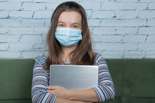 Gezichtsmasker gebruiken tijdens het werken met laptop op kantoor