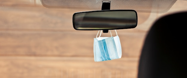 Gezichtsmasker hangend aan de achteruitkijkspiegel in de auto