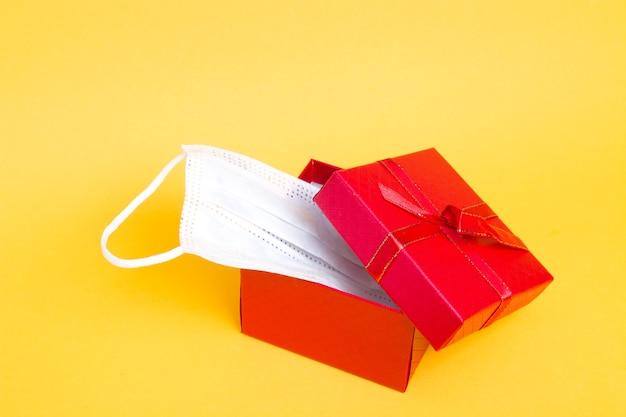 Gezichtsmasker in een rode geschenkdoos op een gele achtergrond kopie ruimte
