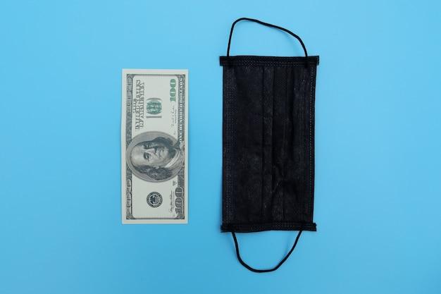 Gezichtsmasker ligt op bankbiljet van 100 dollar op blauwe achtergrond