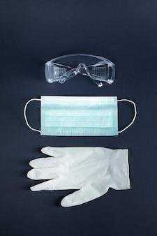 Gezichtsmasker met bril en latex handschoenen ter bescherming van het coronavirus
