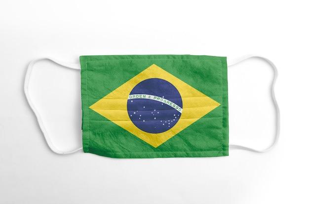 Gezichtsmasker met gedrukte vlag van brazilië, op witte achtergrond, geïsoleerd.
