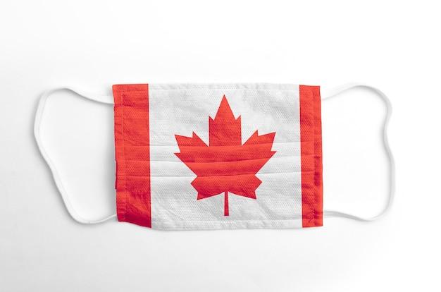 Gezichtsmasker met gedrukte vlag van canada, op witte achtergrond, geïsoleerd.