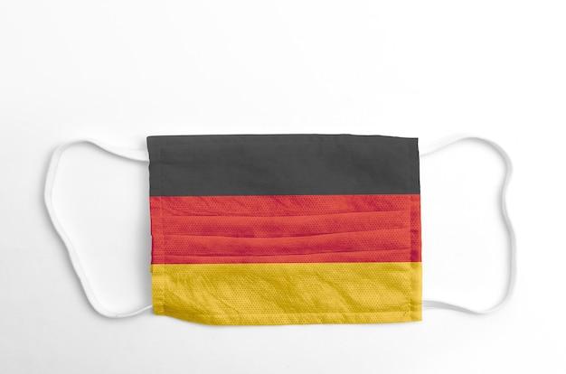 Gezichtsmasker met gedrukte vlag van duitsland, op witte achtergrond, geïsoleerd.