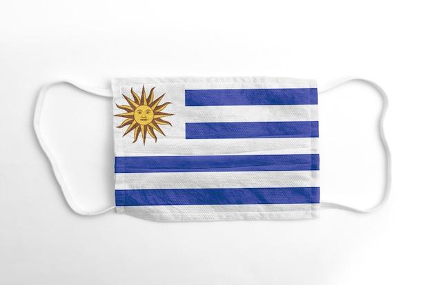 Gezichtsmasker met gedrukte vlag van uruguay, op witte achtergrond, geïsoleerd.
